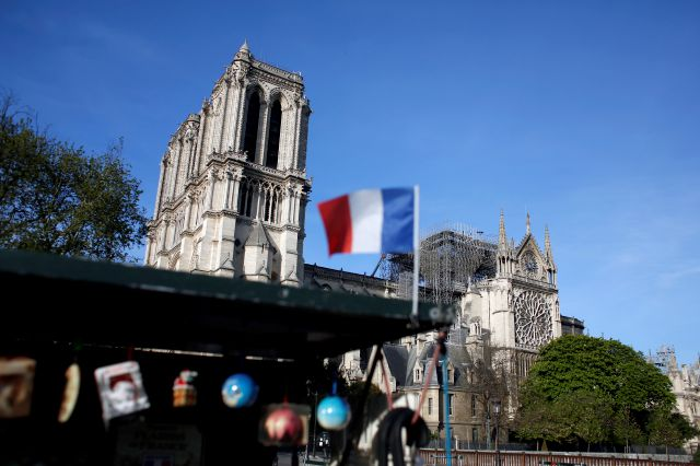 "A French flag flaps in front of Notre Dame cathedral, in Paris, Wednesday, April 17, 2019. Notre Dame Cathedral would have been completely burned to the ground in a ""chain reaction collapse"" had firefighters not moved rapidly in deploying their equipment to battle the blaze racing through the landmark monument, a Paris official said Wednesday. (AP Photo/Thibault Camus)"