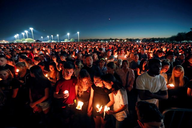 People attend a candlelight vigil for the victims of the Wednesday shooting at Marjory Stoneman Douglas High School, in Parkland, Fla., Thursday, Feb. 15, 2018. Nikolas Cruz, a former student, was charged with 17 counts of premeditated murder on Thursday. (AP Photo/Gerald Herbert)