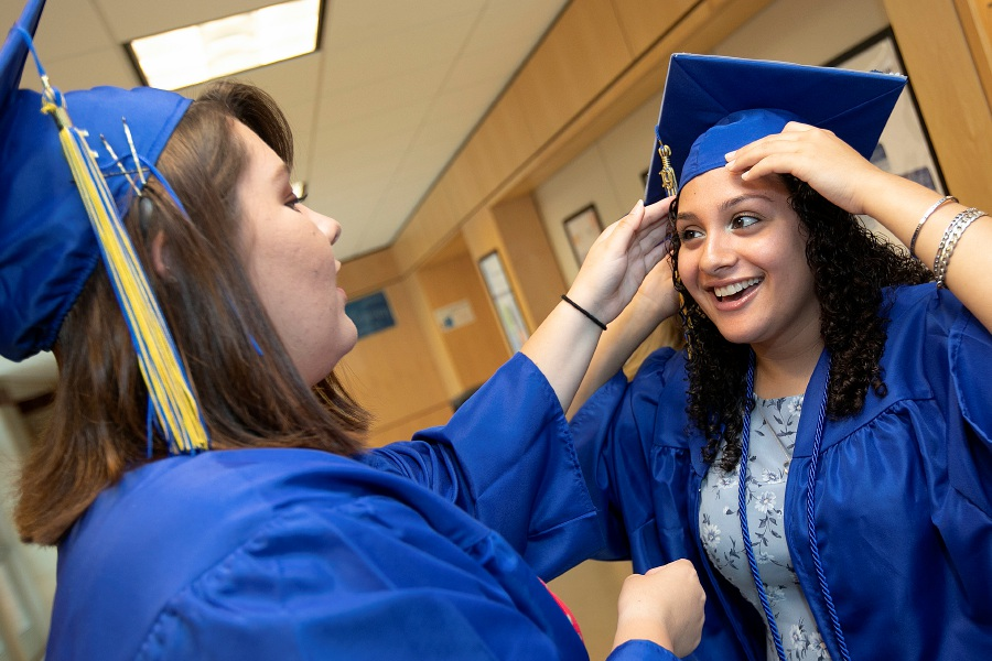 Hannah Jawor, 18, left, helps her friend  Jenna Parillo, 18, with her cap prior to graduation ceremonies at Wilcox Technical High School in Meriden Monday. See photos and story on A6. Dave Zajac, Record-Journal