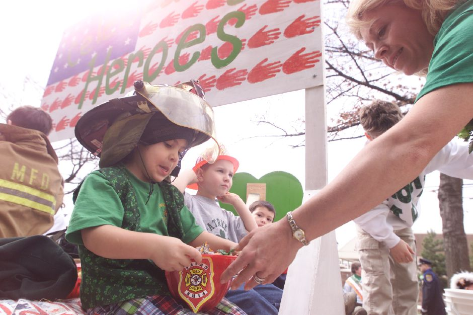 Faith Morico, right, hands a plastic firefighters hat full of candy to her son Anthony Morico, left, as they prepared to begin rolling in the St. Patrick