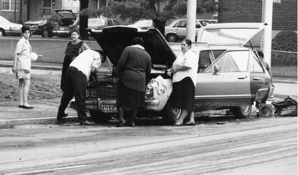 File photo - A family in front of 140 Pratt St. works to clean out a car and get it to start after being stuck in the 1992 flood.