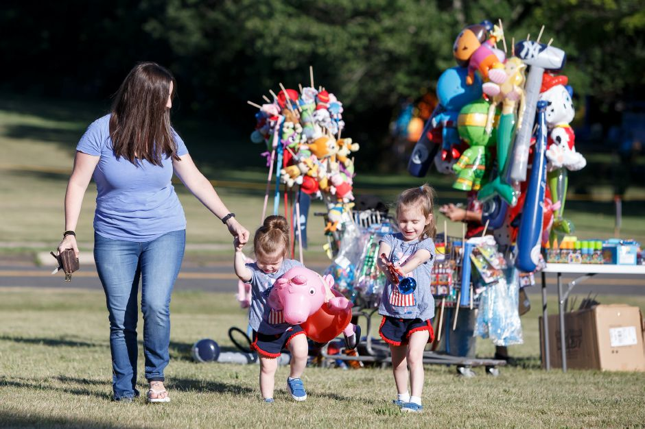 Melissa Stensland walk with daughters Ave 2 and Olivia 5 after picking up some toys Saturday during the Wallingford Fireworks display at Sheehan High School in Wallingford July 7, 2018 | Justin Weekes / Special to the Record-Journal