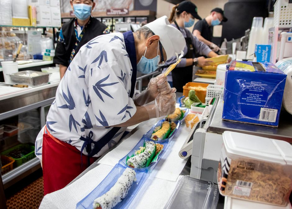 Thein Pe adds the finishing touches to the sushi as he prepares them for customers at Tops Marketplace in Southington on June 30, 2020. Aaron Flaum, Record-Journal
