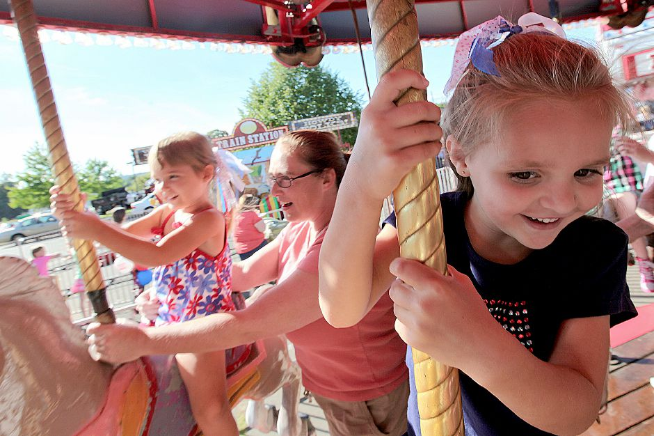 Amanda Thompson, 5, clings to the Merry-Go-Round while her little sister, Emily Thompson, 3, sits near her Aunt, Jackie Dunham. All are Southington residents at the Cheshire