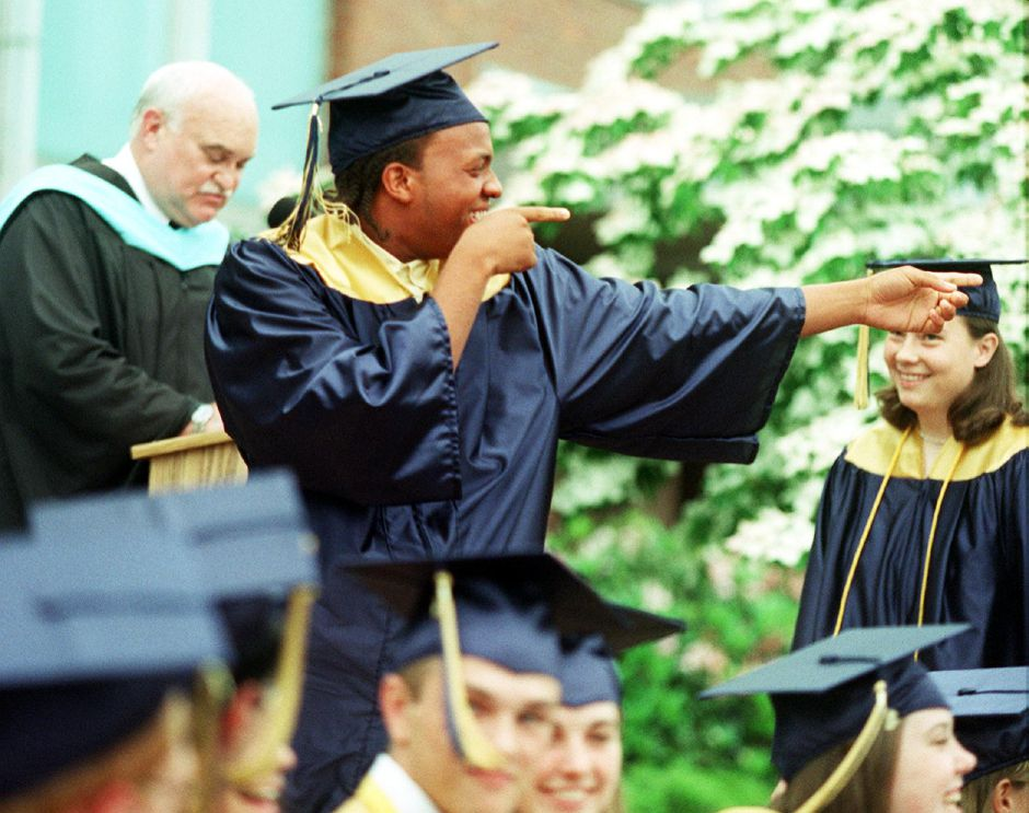 Robert Anthony Grace, Jr. gestures to the crowd as he walks up to receive his diploma at Platt High School graduation Thurs., June 15, 2000. On the left is school principal Timothy Gaffney.
