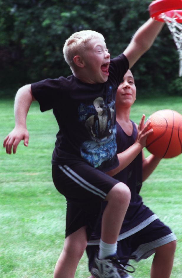 Broody Neilson attempts to stop stop his friend Daniel Otero, with the ball from making a basket in their game at a picnic for the Challenger Little Leage for handicapped children June 24, 2000. The picnic was held for players, parents and friends to celebrate the end of their season. Broody was a player in the Challenger Little Leage.