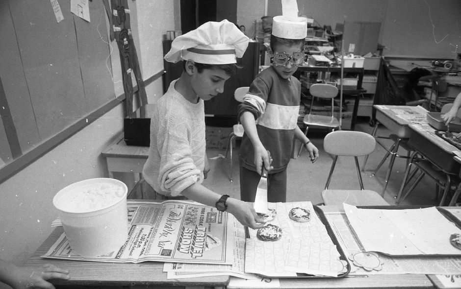 RJ file photo - Parker Farms School fifth-graders Jarad Golitki, 10, and Jason Lord, 11, prepare miniature pizza for sale at the school as art of a class project, March 1989.