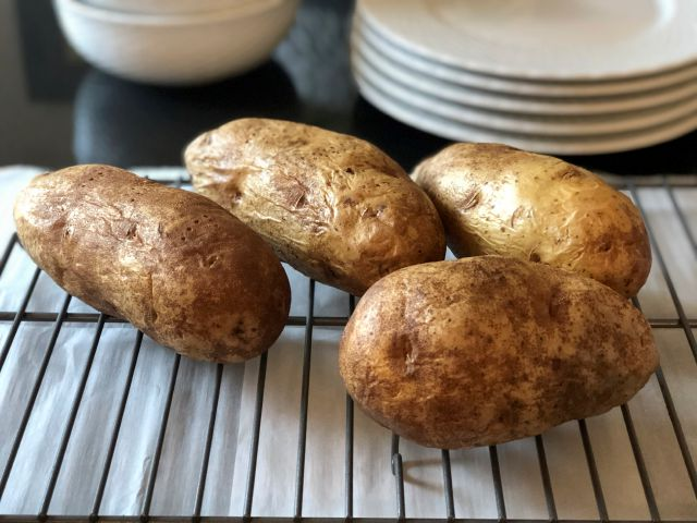 This Dec. 31, 2019 photo shows four baked potatoes resting on a rack in Amagansett, N.Y. Preheat the oven to 350 degrees Fahrenheit and place a sheet of heavy-duty aluminum foil on the bottom shelf of the oven in case any of the juices drip. After washing and drying the potatoes, coat them with either a little regular Crisco shortening or olive oil. Then prick them four or five times with a fork to let steam escape while they are baking. After an hour of baking, stick the end of a...