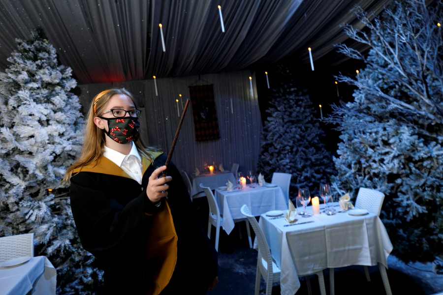 Payton Vogt, 12, of Southington, waves a wand while wearing a wizard robe as she tours the new Harry Potter inspired dining room at Cava in Southington Thursday.Dave Zajac, Record-Journal
