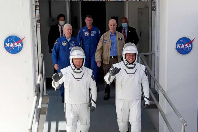NASA astronauts Douglas Hurley, left, and Robert Behnken walk out of the Neil A. Armstrong Operations and Checkout Building on their way to Pad 39-A, at the Kennedy Space Center in Cape Canaveral, Fla., Saturday, May 30, 2020. The two astronauts will fly on a SpaceX test flight to the International Space Station. For the first time in nearly a decade, astronauts will blast into orbit aboard an American rocket from American soil, a first for a private company. (AP Photo/John Raoux)