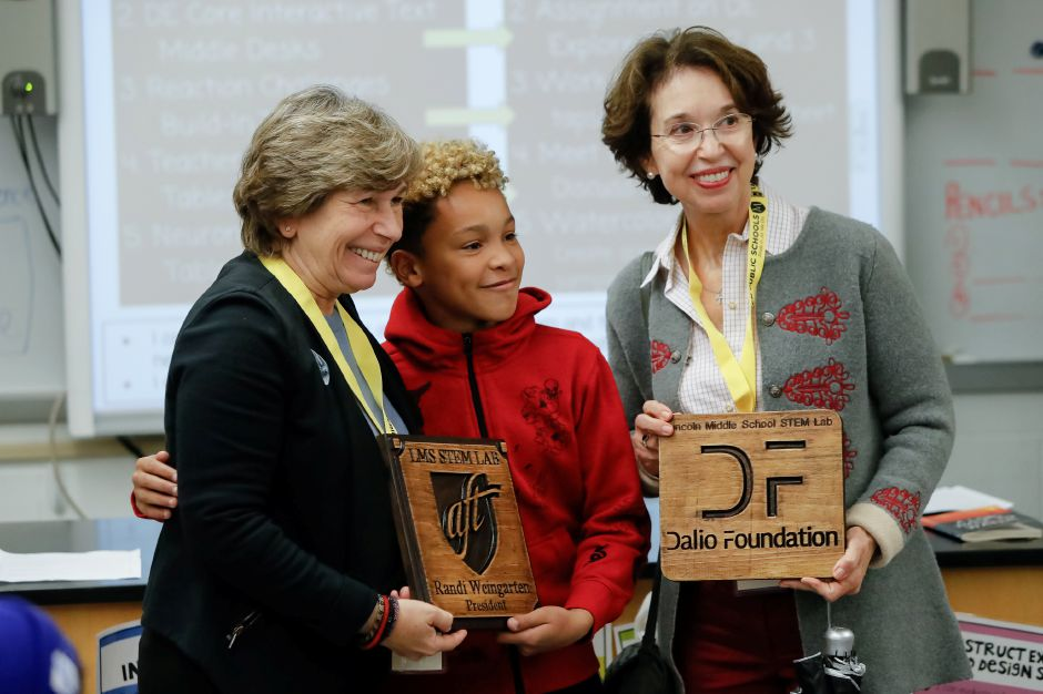 Justin Black, 12, presents plaques to Randi Weingarten, president of the American Federation of Teachers (left) and Barbara Dalio, president of the Dalio Foundation, at Meriden's Lincoln Middle School in 2018. | File photo.