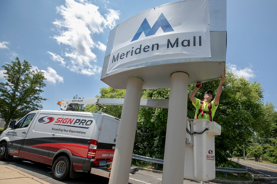 Spencer Browne, a worker for Southington based Sign Pro, takes measurements for new signage after attaching a temporary sign at the north entrance of the newly named Meriden Mall in Meriden Thursday. Dave Zajac, Record-Journal