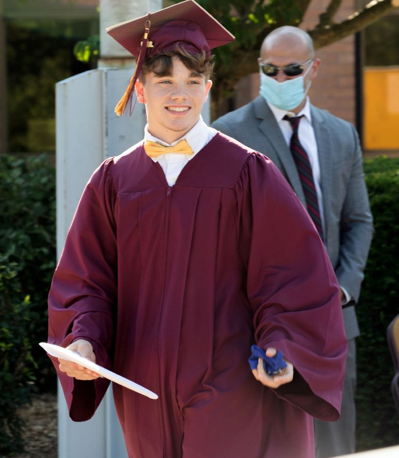 Left: Sheehan graduate Justin Moore walks across the stage after he received his diploma  Tuesday during a drive up graduation at the school. Right: Graduate Olivia Fonteyn turns her tassel after she received her diploma. Photos by Aaron Flaum,. Record-Journal