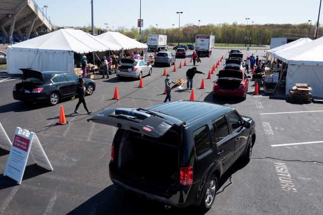 Cars line up at a Foodshare distribution center at Rentschler Field in East Hartford, Conn., Thursday, May 7, 2020, during the coronavirus pandemic. Foodshare has been offering the emergency drive-thru distribution for three weeks and said that as the lines continue to grow, they provide food to approximately 1,200 households per day. (AP Photo/Mark Lennihan)