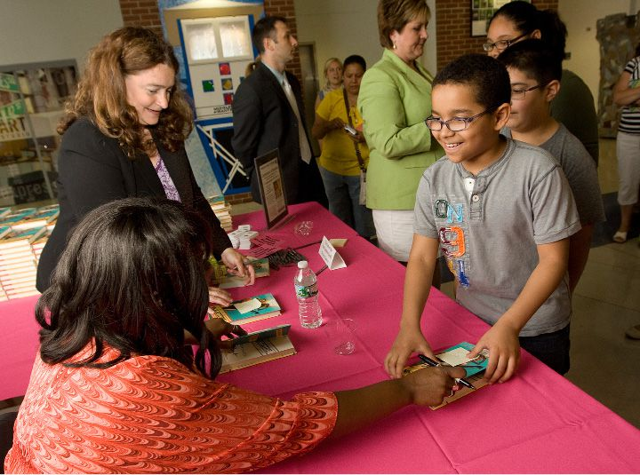 Academy award winning actress and author, Octavia Spencer, seated at left, signs a book for Hanover School fourth grader, Brayhan Germoso, 9, as Kim Carbone-Pandiani, a Board of Education member, assists during an end-of-year celebration for students who read a million words throughout the year at Lincoln Middle School, Monday, June 16, 2014. | Dave Zajac / Record-Journal