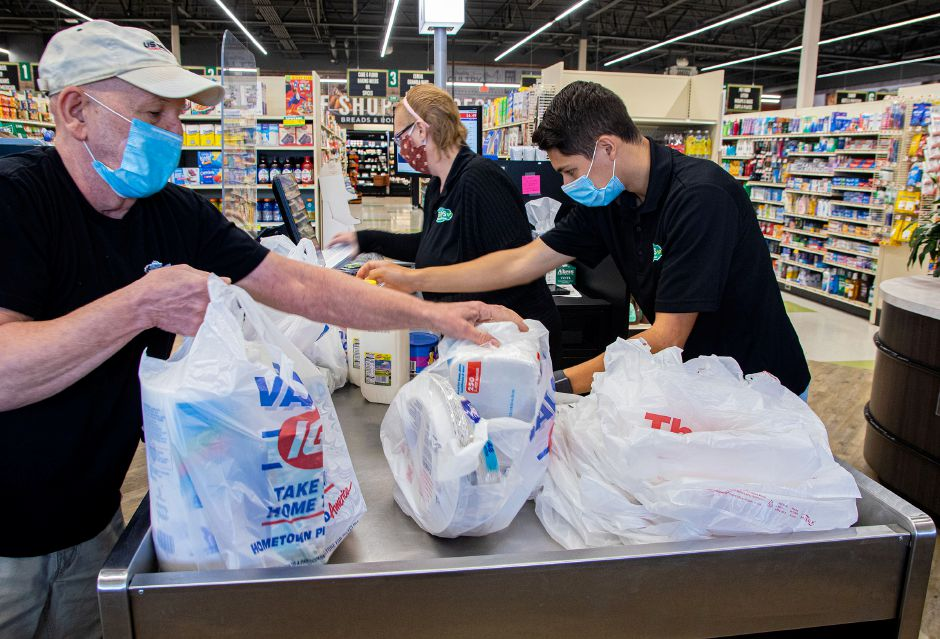 Mike Rogers of Southington, puts his bags into his carriage as Becky Reopel and Jared Rivera scan and package the remainder of his groceries on Tuesday, June 30, 2020. Aaron Flaum, Record-Journal