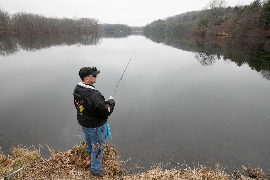 Johnny Berrios, of Wallingford, waits for a bite while fishing a calm Mackenzie Reservoir in Wallingford on Friday.