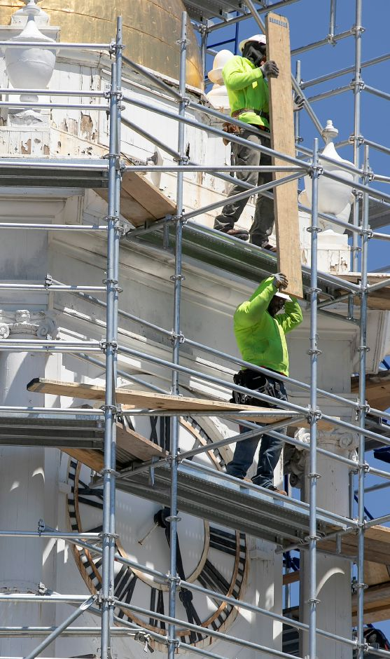 Workers from Enterprise Scaffolding, Inc., set up scaffolding for the clock tower renovation project.