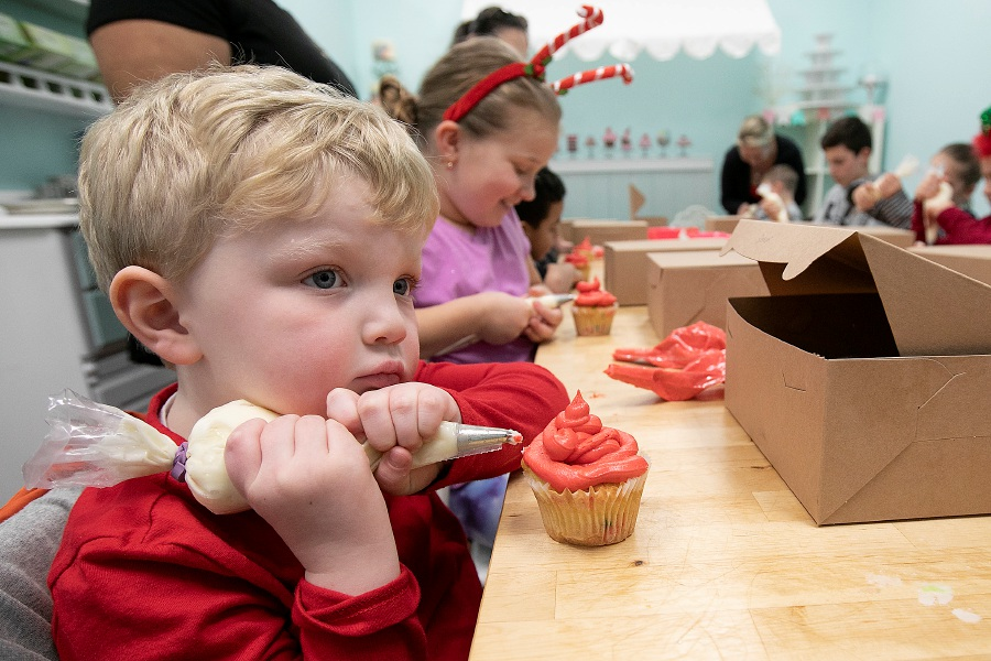 Spencer Sheades, 4, of Wallingford, waits for help from mother Jennifer before frosting his cupcake during a cupcake decorating class at Alyssa