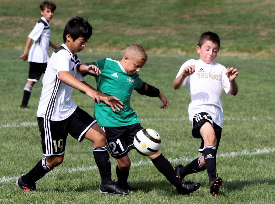 WYSL Tigers Ethan Hayes passes the ball as he is teamed up by Trumbull United