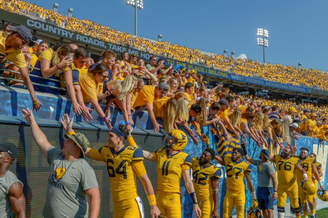 FILE - In this Oct. 6, 2018, file photo, West Virginia players high-five fans after defeating Kansas 38-22 in an NCAA college football game in Morgantown, W. Va. The crippling coronavirus pandemic has brought the entire world — including the sports world — to a standstill, and it shows no sign of going away anytime soon. That has left fans, stadium workers, team owners, sponsors and yes, even players, wondering what life will be like when games finally resume. (AP Photo/Craig Hudson, File)