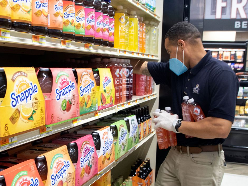 Above left: Polar Beverage distributor Marquet Reed outfitted with a mask and a pair of gloves, works on stocking beverages on the shelves at Tops Marketplace   Tuesday. Above right: Mike Rogers of Southington, check-outs the paper products that are available at Tops Marketplace in Southington as he shops on Tuesday.