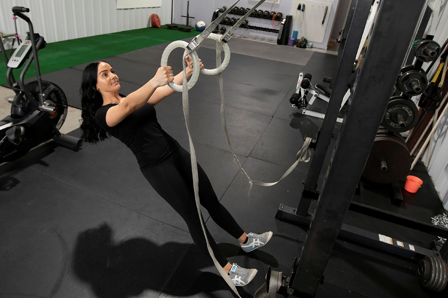Erika Hurst, owner of StrongHer Fitness, does a few ring row reps on Thursday, June 11, inside the gym located at 168 North Plains Industrial Road, Suite 46, Wallingford. StrongHer Fitness is set to reopen today. Photos by Dave Zajac, Record-Journal