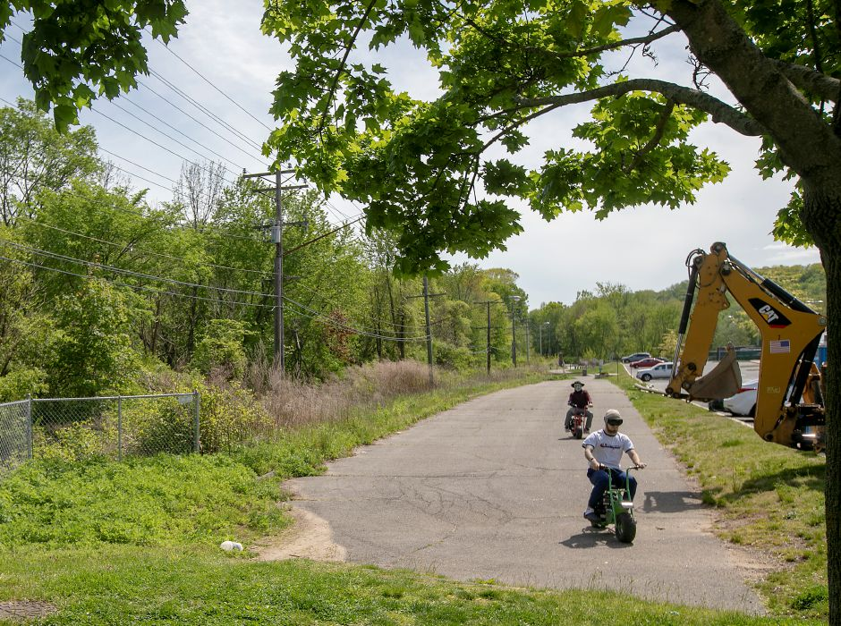Minibike riders cruise down an asphalt path adjacent to Platt High School at the end of the Meriden Linear Trail off Coe Avenue, Tues., May 19, 2020. The City of Meriden's Engineering Department will continue the trail along Coe Avenue to the Bradley Avenue Bridge that overlooks Harbor Brook. The extension of the trail should be completed by the end of the summer. Dave Zajac, Record-Journal