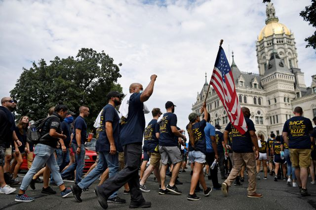 "FILE — In this July 23, 2020, file photo, people participating in a ""Back the Blue"" rally to show support for law enforcement officers march toward the State Capitol, in Hartford, Conn. The Connecticut State Police Union is asking a federal judge to declare parts of the state"