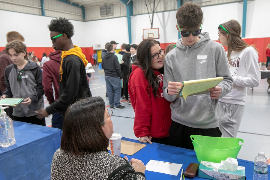 Sheehan sophomore Alexa Fasano looks over the shoulder of fellow classmate Gabriel Goodwin, who checks over his monthly budget with Sorrina Salvatore, business relationship officer at Ion Bank. The students were participating in the Credit for Life event  at Wallingford Parks and Recreation, Tues., Feb. 25, 2020. Credit for Life is a collaborative initiative providing students with experiences that resemble real life situations. Dave Zajac, Record-Journal
