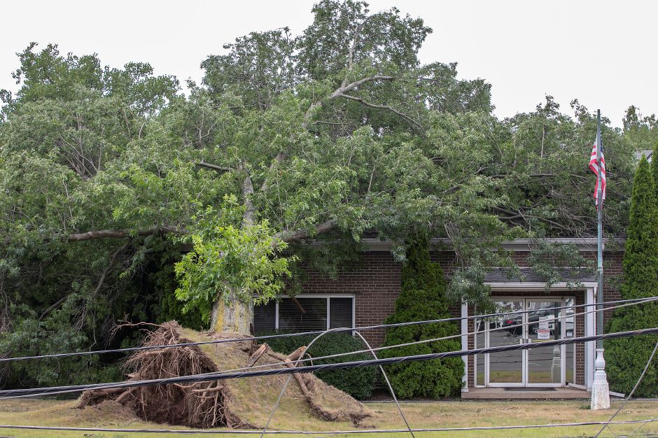 A fallen tree rests on the roof of Supreme-Lake Manufacturing, Inc. at 455 Atwater St. in Southington, Thurs., Aug. 6, 2020. A snapped utility pole and other fallen trees nearby brought down wires in front of the building. Dave Zajac, Record-Journal