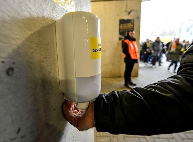In this Feb. 29 photo, a fan cleanses his hands at a new disinfection station in the stadium before the German Bundesliga soccer match between Borussia Dortmund and SC Freiburg in Dortmund, Germany. Associated Press