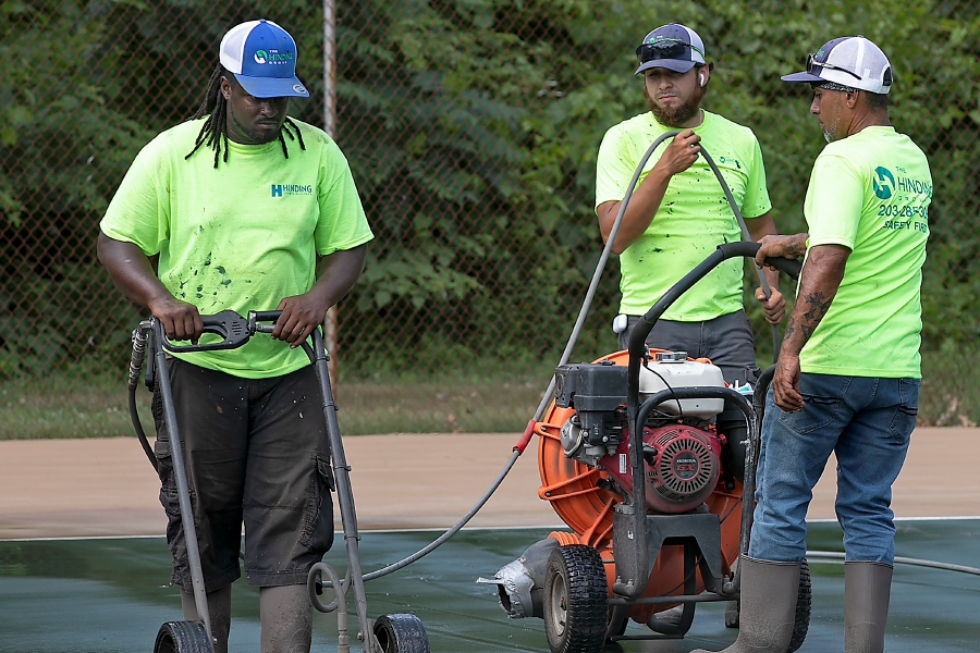 Workers for West Haven based Hinding Sports Builders scrub the tennis courts at Veterans Memorial Park in Southington as improvements continue there Monday afternoon, Jul. 6, 2020. Dave Zajac, Record-Journal