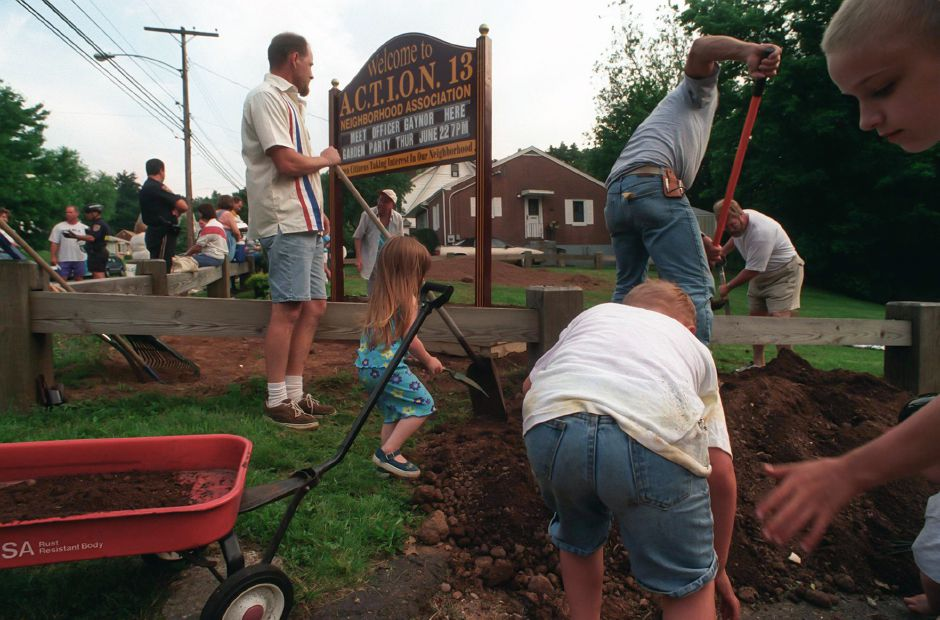 Neighbors help shovel dirt and plant flowers around Action 13