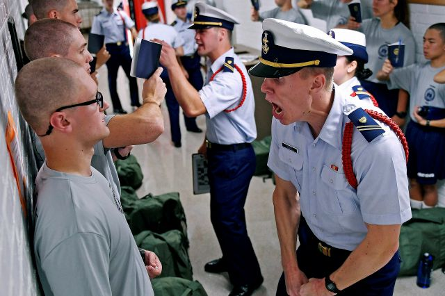 FILE - In this July 1, 2019, file photo, Whisky 2 company Cadre Jacob Denns, right, shouts instructions to swab Nicolas Fisher, left, of Pelham, N.H., on the first day of a seven-week indoctrination to military academy life for the Class of 2023 at the U.S. Coast Guard Academy in New London, Conn. The school, like other service academies and military training centers, has made major changes because of the coronavirus pandemic. That means the eight weeks of boot camp for new cadets,...