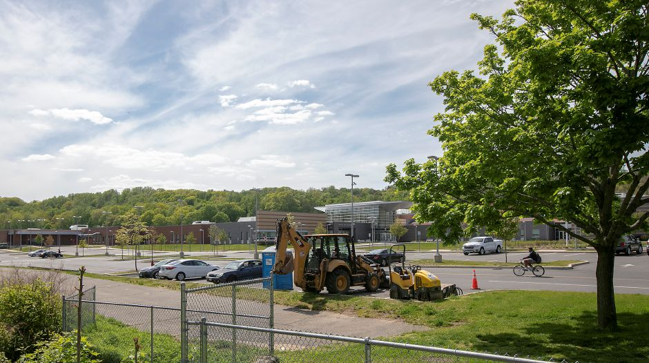 A bicyclist, right, pedals through the Platt High School parking lot near the end of the Meriden Linear Trail, bottom, Tues., May 19, 2020. The City of Meriden's Engineering Department will continue the trail along Coe Avenue to the Bradley Avenue Bridge that overlooks Harbor Brook. The extension of the trail should be completed by the end of the summer. Dave Zajac, Record-Journal