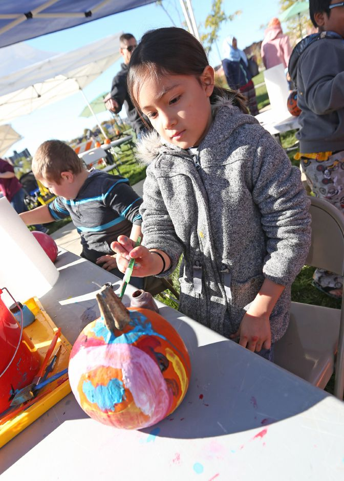 Emily Maldonado, 7, of Meriden, paints a pumpkin on the Meriden Green during the last farmer's market of the season on Saturday, Oct. 20, 2019. Emily J. Tilley, special to the Record-Journal.