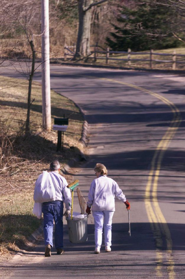 RJ file photo - Dr. Luis Alonso, left, and his wife, Sheila Alonso, carry a full trash can up Mapleview Road in Wallingford after collecting trash, March 1999. The two, along with some neighbors, participate in the Adopt-a-Road program.