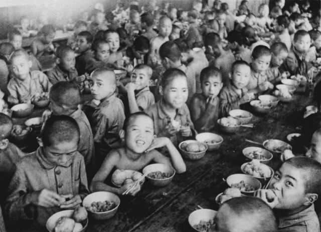 War orphans eat together at an orphanage in Tokyo in 1946. In Japan, war orphans were punished for surviving. They were bullied. They were called trash, sometimes rounded up by police and put in cages. Some were sent to institutions or sold for labor. They were targets of abuse and discrimination. A 1948 government survey found there were more than 123,500 war orphans nationwide. But orphanages were built for only for 12,000, leaving many homeless. (Kyodo News via AP)