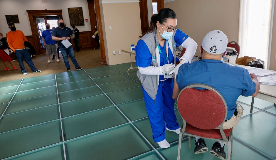 FILE: Griffin Hospital nurse Carrie Cotto administers the Johnson & Johnson vaccine to Reinaldo Vazquez, of Meriden, during a clinic at the Augusta Curtis Cultural Center on East Main Street in Meriden, Wed., Apr. 7, 2021. Dave Zajac, Record-Journal