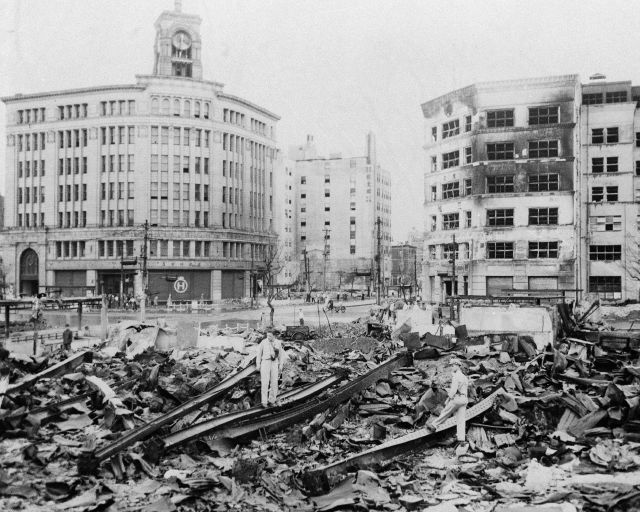 Unidentified U.S. Army men look over the bombed section of Tokyo, Japan