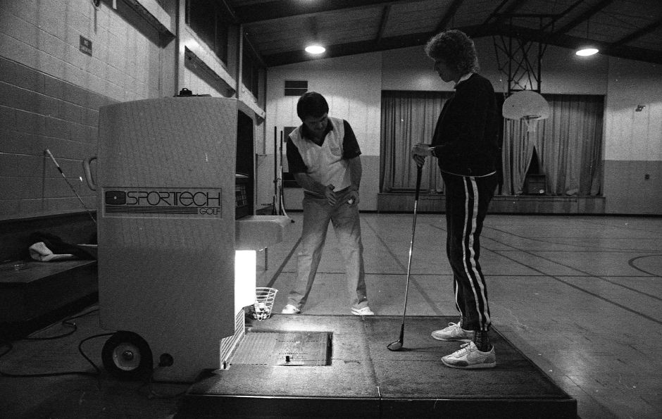 RJ file photo - Rusty Spooner, golf professional and owner of Northeast Golf & Tennis Educational Center in Meriden, instructs Lois Doherty with the aid of the computerized Sportech golf swing analyzer, at the Wallingford Recreation Department Feb. 1989.