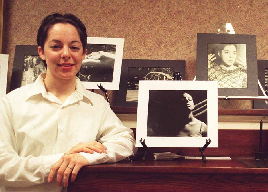 RJ file photo - Kim Lavorgna, a senior at Southington High School, shows off some photographs she has on display at Southington Savings Bank this month, Feb. 1999.