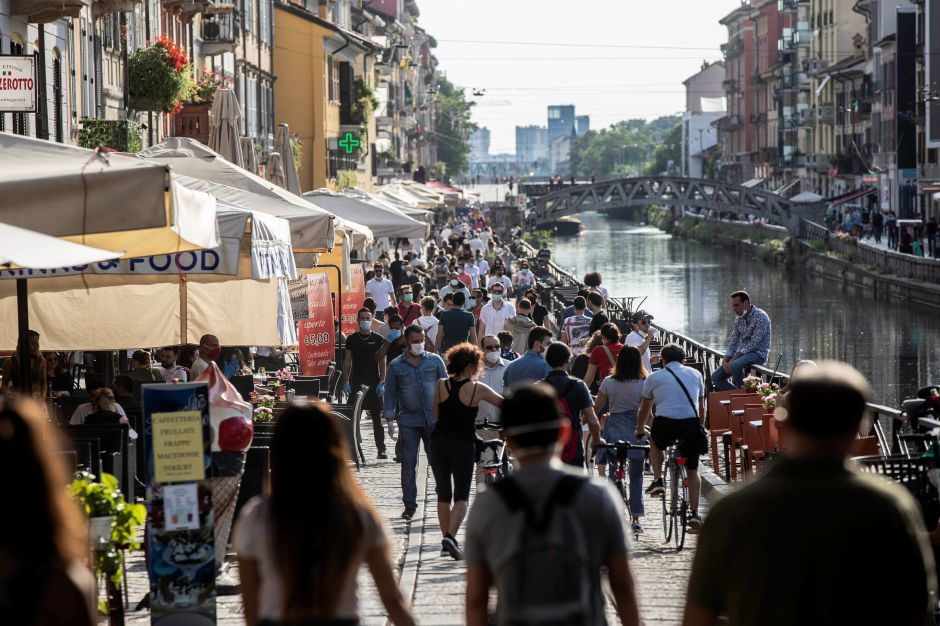 People take a walk and relax at the Naviglio Grande canal, in Milan, Italy, Sunday, May 24, 2020. Europeans and Americans soaked up the sun where they could, taking advantage of the first holiday weekend since coronavirus restrictions were eased, while European governments grappled with how and when to safely let in foreign travelers to salvage the vital summer tourist season. Italy, which plans to open regional and international borders on June 3 in a bid to boost tourism, is only...