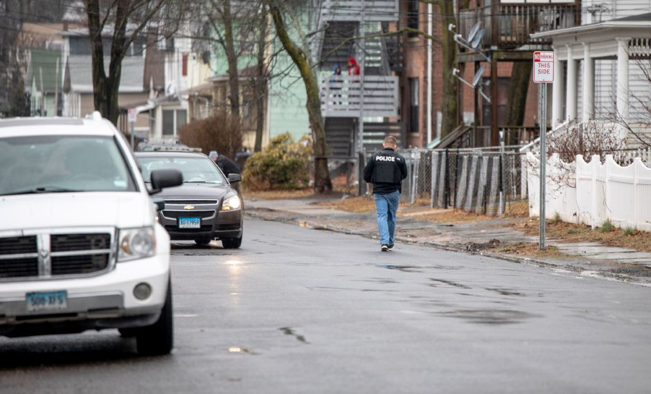 Police canvas homes in the area of the intersection of Sherman Avenue and Warren Street in Meriden after a report of a pedestrian being shot at the intersection on Feb. 13, 2020. | Devin Leith-Yessian/Record-Journal