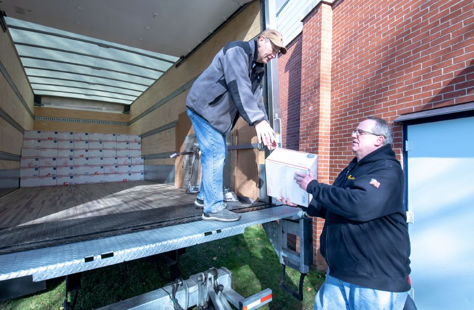 From left, George Millerd and Tom Deegan load care packages into a truck at the New Britain Veterans of Foreign Wars post for the Hero Boxes care package packing day on Nov. 9, 2019. The Berlin-based non-profit sends hundreds of care packages to soldiers serving in war zones each year. | Devin Leith-Yessian/Berlin Citizen