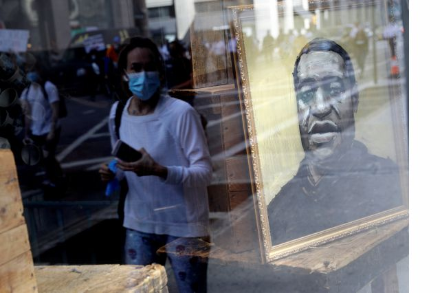 Protesters are reflected in a store window where a portrait of George Floyd is displayed in Manhattan, New York, Monday, June 1, 2020. New York City imposed an 11 p.m. curfew Monday as the nation