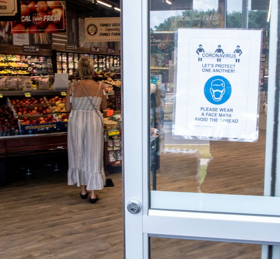 A sign at the entrance of Tops Marketplace in Southington is on display at the entrance to remind shoppers to wear a mask to help prevent the spread of Covid-19. Aaron Flaum, Record-Journal