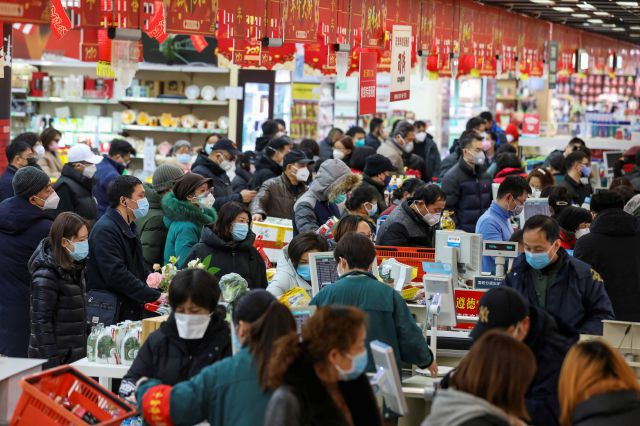 Shoppers wearing face masks pay for their groceries at a supermarket in Wuhan in central China