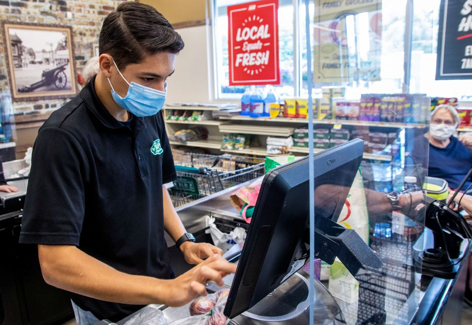 Cashier Jared Rivera works behind a piece of plexiglass as he cashes out Jim and Rita Gagnon of Southington at Tops Marketplace on Tuesday, June 30, 2020. The plexiglass was installed to protect the cashiers from the spread of Covid-19. Aaron Flaum, Record-Journal